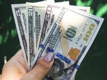 Bankbiljetten van dollarrekeningen in vrouwelijke handen royalty-vrije stock fotografie