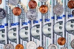 Bankbiljetten van honderd dollars en vele muntstukken Royalty-vrije Stock Afbeeldingen