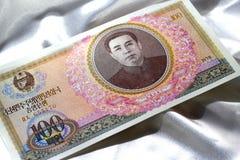 Bankbiljetten van Noord-Korea op een witte satijnachtergrond Stock Afbeeldingen
