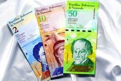 Bankbiljetten van van Venezuela op een witte satijnachtergrond Stock Fotografie