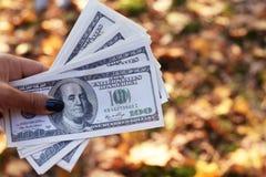 Bankbiljettengeld honderd dollars in de hand van een meisje stock foto's