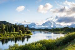 Banken van rivier met bergen stock afbeeldingen