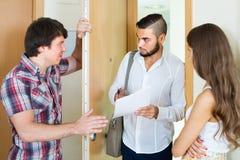 Banker and couple talks in doorway Stock Photo