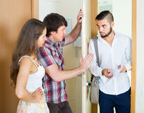 Banker and couple talks in doorway Royalty Free Stock Photo