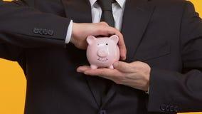 Banker, der piggybank mit beiden Händen, Zuverlässigkeit und Sicherheit der Investition hält stock video footage