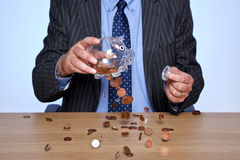 Banker, der seine piggy Querneigung leert Stockfotos