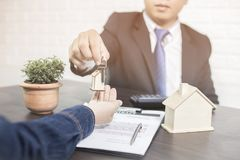 Banker give home key to buyer after finishing purchase house. In bank royalty free stock photo