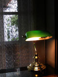 Banker's Lamp. Banker style lamp with green glass and brass... lighting a semi-dark room with lacy curtains Stock Photography