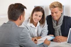 Banker talking to young couple in office Royalty Free Stock Images