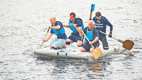 Bankers working for charity in raft race. Royalty Free Stock Image