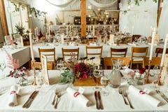 banket Het feestelijke lijst plaatsen Huwelijkslijst met de herfstbloemen en kaarsen die wordt verfraaid stock afbeeldingen