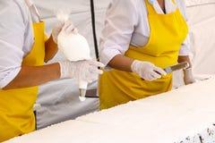 Banketbakker die smakelijke cupcake met boterroom verfraaien de banketbakker ` s dient witte handschoenen in zette een witte room royalty-vrije stock afbeeldingen