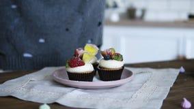 Banketbakker smakelijk verfraaien, verfraaid buitensporig cupcakes Suikerglazuursuiker op cakes met verse aardbeien wordt bestroo stock footage