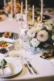 Banketlijst voor diner met bloemboeketten wordt verfraaid van dahlia en witte kaarsen die Op de lijst, de glazen, het bestek en w stock fotografie
