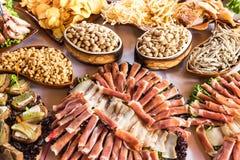 Bankettisch mit Fleischwaren, Pistazien, Oliven, Trockenfisch, Chips und anderen Snäcken Stockbild
