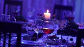 Banketttabell i en restaurang med exponeringsglas och en stearinljus, ett exponeringsglas med rött och vitt vin på en banketttabe lager videofilmer