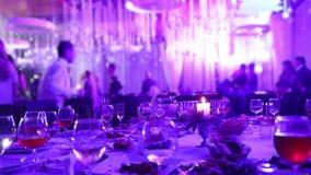 Banketttabell i en restaurang med exponeringsglas och en stearinljus Folket dansar mot bakgrunden av tabellen sallader för frukts stock video