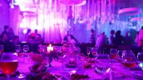 Banketttabell i en restaurang med exponeringsglas och en stearinljus Folket dansar mot bakgrunden av tabellen sallader för frukts lager videofilmer