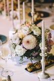 Banketttabellen för matställe dekorerade med blommabuketter av dahlia- och vitstearinljus På tabellen plat exponeringsglas, besti Royaltyfri Fotografi