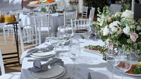 Bankiet z ampuła stołami z białymi tablecloths dla różnorodność wyśmienicie naczyń, kwiatów przygotowania z różami zbiory