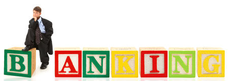 Banking. Handsome seven year old american boy in over sized suit with the word banking in giant alphabet blocks Stock Photos