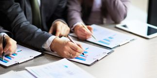 Banking business or financial analyst desktop accounting charts, pens indicates in the graphics. Banking business or financial analyst desktop accounting charts Royalty Free Stock Photos