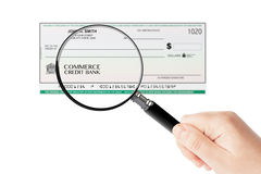 Banking Check with magnifier glass in hand Stock Images