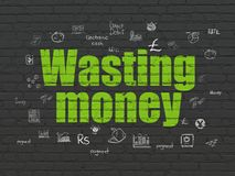 Banking concept: Wasting Money on wall background. Banking concept: Painted green text Wasting Money on Black Brick wall background with  Hand Drawn Finance Royalty Free Stock Photography