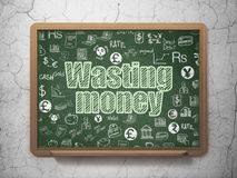 Banking concept: Wasting Money on School board background. Banking concept: Chalk Green text Wasting Money on School board background with  Hand Drawn Finance Royalty Free Stock Photo