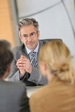 Banking consultant listening to clients. Consultant listening to clients in meeting stock photo