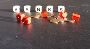 Banking crisis. Photograph of white cubes spelling out the word BANKS, with coins, toy houses and red dice in the foreground. Dark textured background Royalty Free Stock Image