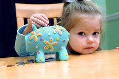 Banking Miniature Style. Small girl rests her head on a table top as she inserts coins into her aqua colored piggy bank stock photo