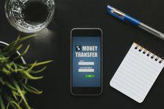Front view of money transfer app in a mobile phone screen over a black business table. Banking mobile phone app ready for money transfer at a workplace in the stock image