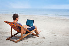 Banking online. Business man with laptop on the beach, banking online royalty free stock photography