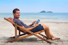 Banking online. Portrait of happy business man with tablet on the beach Stock Photography