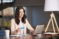 Banking online. Shot of a happy young businesswoman doing her online banking while working in the office stock images