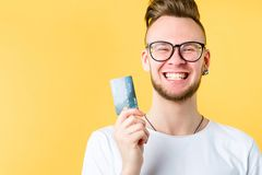 Banking service business loan startup financing. Banking service. Business loan. Startup financing. Portrait of young ambitious guy holding credit card, smiling stock images