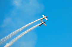 Banking Stunt Planes. Two stunt planes make a synchronized banking maneuver while trailing smoke at an air show demonstration Royalty Free Stock Images