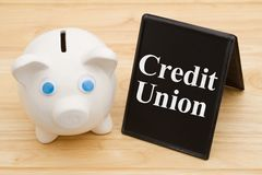 Banking using a credit union. A piggy bank on a desk with chalkboard with text Credit Union royalty free stock photos