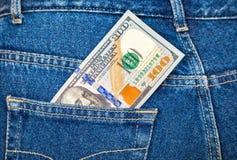 Banknot sto amerykańskich dolarów w cajgach wkładać do kieszeni Fotografia Royalty Free