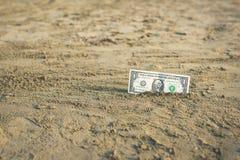 Banknot wartość jeden dolar w piasku na plaży Pojęcie tani wakacje i podróż zdjęcia royalty free