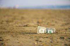 Banknot wartość jeden dolar w piasku na plaży Pojęcie tani wakacje i podróż obrazy stock