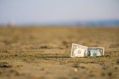 Banknot wartość jeden dolar w piasku na plaży Pojęcie tani wakacje i podróż fotografia royalty free