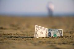 Banknot wartość jeden dolar w piasku na plaży Pojęcie tani wakacje i podróż fotografia stock