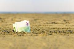 Banknot wartość sto euro w piasku na plaży Pojęcie tani wakacje i podróż zdjęcia royalty free