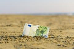 Banknot wartość sto euro w piasku na plaży Pojęcie tani wakacje i podróż zdjęcie stock