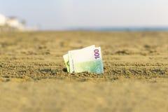 Banknot wartość sto euro w piasku na plaży Pojęcie tani wakacje i podróż obraz stock