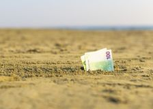 Banknot wartość sto euro w piasku na plaży Pojęcie tani wakacje i podróż zdjęcia stock
