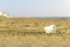 Banknot wartość sto euro w piasku na plaży Pojęcie tani wakacje i podróż fotografia royalty free