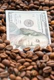 Banknote of 100 American dollars, between grains of coffee. Business concept for the purchase, sale, delivery and distribution of stock photography
